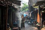 A woman passes by a coking coal oven at Maniktola slum in Kolkata during 21 days lock down in India due to covid 19 pandemic. Kolkata, West Bengal, India. Arindam Mukherjee.