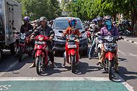 Yogyakarta, Java, Indonesia.  Street Traffic, Motorbikes.  Note Breathing Mask on Right.