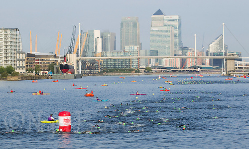 31 JUL 2011 - LONDON, GBR - Competitors swim along Royal Victoria Dock from in front of the Excel Centre  and with Canary Wharf behind during the Virgin Active London Triathlon .(PHOTO (C) NIGEL FARROW)