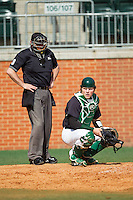 Charlotte 49ers catcher Patric King (28) looks to the dugout for the sign as home plate umpire Barry Chambers looks on during the game against the Canisius Golden Griffins at Hayes Stadium on February 23, 2014 in Charlotte, North Carolina.  The Golden Griffins defeated the 49ers 10-1.  (Brian Westerholt/Four Seam Images)