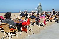Voorjaar in Scheveningen. Mensen zitten bij een strandtent
