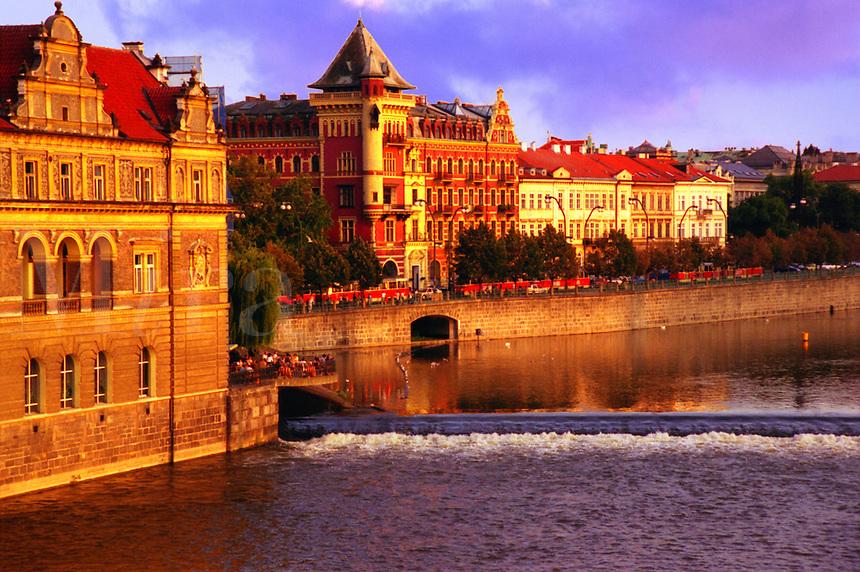 Late afternoon sunlight along the emabankment of the river Vtlava traversing Prague (Czech Republic)