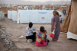 DOMIZ, IRAQ: Women and children sit outside their tents in the Domiz refugee camp..Over 7,000 Syrian Kurds have fled the violence in Syria and are living in the Domiz refugee camp in the semi-autonomous region of Iraqi Kurdistan...Photo by Ali Arkady/Metrography