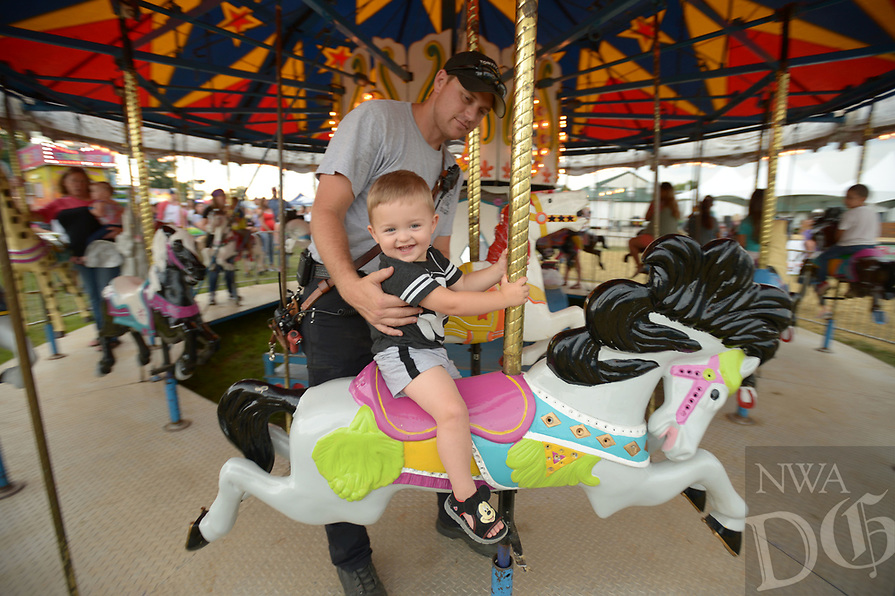 NWA Democrat-Gazette/ANDY SHUPE<br /> Aiden Pianalto, 2, gets a hand from his father, Justin Pianalto, Wednesday, Aug. 8, 2018, while riding the merry-go-round during the 120th annual Tontitown Grape Festival in Tontitown. The festival continues through Saturday. The festival features a nightly midway, an arts and crafts fair, spaghetti dinners and live entertainment.