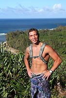 A hiker on the Kalalau Trail along the Na Pali coastline, with Ke'e Beach in the distance, northern Kaua'i.