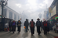Tibetan Buddhist pilgrims circumambulate the Barkhor alleys in a clockwise direction around the Jokhang Temple during Saga Dawa festival, against the early morning sun and incense smoke, Lhasa, Tibet.