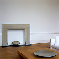 An empty stone fire surround against one wall of the minimalist living room