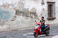 Antigua, Guatemala.  Young Woman on Motorbike, no Helmet.