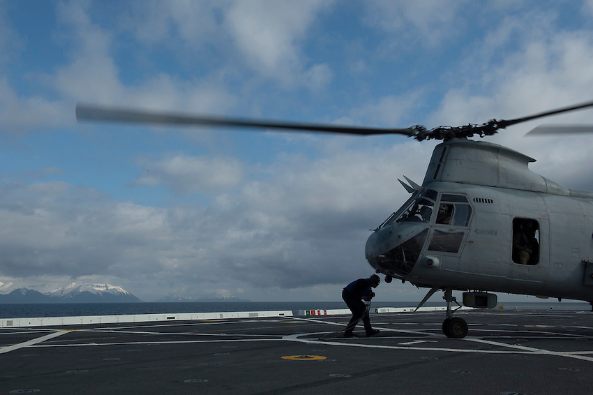 130430-N-DR144-186 COOK INLET, Alaska (April 30, 2013)- Air Department Sailors chock and chain a Marine Corps CH-46 Sea Knight to the deck as San Antonio-class amphibious transport dock ship USS Anchorage (LPD 23) approaches the coast of Alaska. Anchorage is currently en route to its namesake city of Anchorage, Alaska for its commissioning ceremony May 4. (U.S. Navy photo by Mass Communication Specialist 1st Class James R. Evans / RELEASED)