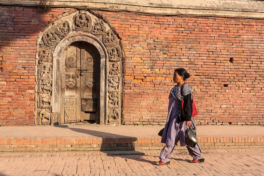 Nepal, Patan.  Nepali Woman Walking by Doorway into Royal Palace Compound, Durbar Square.