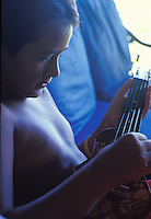 Local Hawaiian boy playing ukulele at home