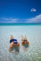 Couple in shallow water at Sapodilla Bay. Providenciales. Turks and Caicos.