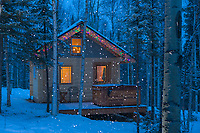 Snow falling around a log cabin tucked in the boreal forest in Fairbanks, Alaska