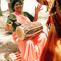 Woman playing an Indian drum for dancers on the beach, Mauritius