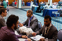 Ali Malik (right), an Army veteran from Queens, New York, and Shevon Morrison, a Navy veteran from Westchester, New York, (center) speak with Uber representatives who asked not to be named at the Recovering Warrior Employment Conference at the Back Bay Event Center in Boston, Massachusetts, USA. The employment conference was organized by Hiring Our Heroes and Wounded Warrior Project. Hiring Our Heroes is an initiative of the US Chamber of Commerce Foundation. Approximately 40 veterans registered for the event, during which they had interviews with a number of different regional and national employers, including GE, Bank of America, Uber, and others.