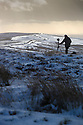 15/01/16<br /> <br /> As the sun reflects off an icy distant road, a photographer stands surrounded by snow covered heather to take landscape photographs of the stunning Staffordshire moorlands near Longnor in The Peak District.<br /> <br /> All Rights Reserved: F Stop Press Ltd. +44(0)1335 418365   +44 (0)7765 242650 www.fstoppress.com