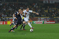 U.S. defender Jay DeMerit and England's Wayne Rooney contest a loose ball during the teams' devut in the 2010 FIFA World Cup. The U.S. and England played to a 1-1 draw in the opening match of Group C play at Rustenburg's Royal Bafokeng Stadium, Saturday, June 12th.