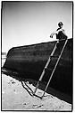 Uzbekistan - Nukus - Man sitting on a stranded boat