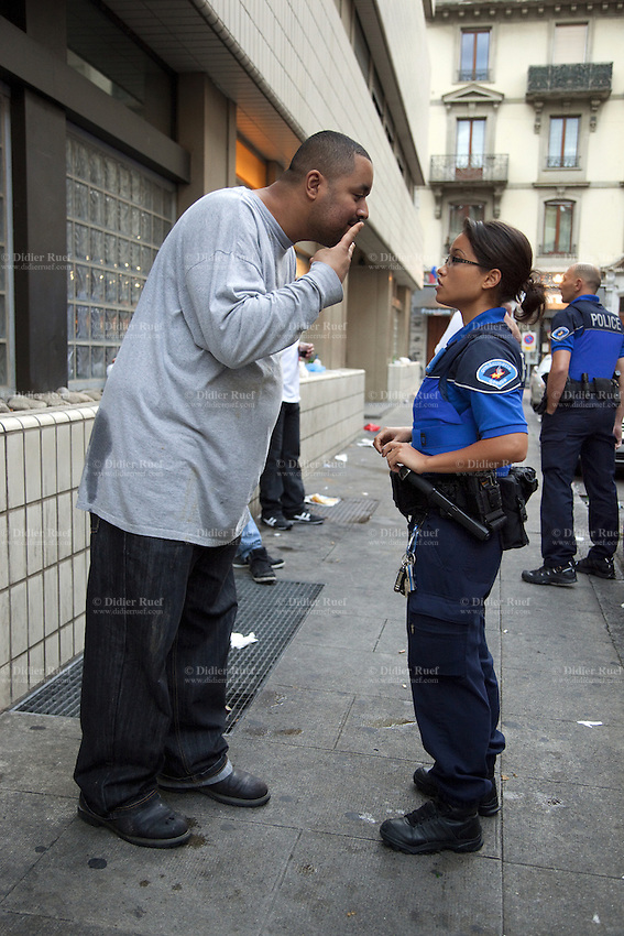 Switzerland. Geneva. Paquis neighborhood. A short police officer talks to a tall drunk man. 7.07.12 © 2012 Didier Ruef..