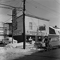 Un jeune livreur de depanneur en velo typique de avec la marchandise en avant, passe dans le rue devant le distributeur de SKODA :  SIMARD AUTO, en fevrier 1963, a Limoilou,  Quebec,<br /> <br /> PHOTO : Agence Quebec Presse