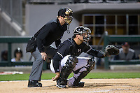 Charlotte Knights catcher Kevan Smith (32) sets a target as home plate umpire Matt McCoy looks on during the game against the Toledo Mud Hens at BB&T BallPark on April 27, 2015 in Charlotte, North Carolina.  The Knights defeated the Mud Hens 7-6 in 10 innings.   (Brian Westerholt/Four Seam Images)
