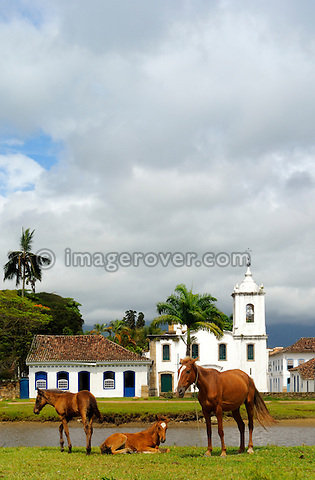 Horses in front of the church Igreja Nossa Senhora das Dores; Paraty, Espirito Santo, Brazil. The beautiful colonial town of Paraty has been a UNESCO World Heritage Site since 1958. Very charming the whitewashed churches and terra-cotta roofs contrast the lush green of the rainforest-clad mountains. --- No signed releases available.