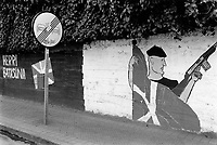 """Spain. Basque Country. Spain. Basque Country. Algorta is a locality within the municipality of Getxo, in the province of Biscay. No overtaking road sign. On the wall, various political graffitis: """" Herri Batasuna """", a man with a basque beret holding a machine gun and the ikurrina flag. The ikurrina flag (in Basque) or ikurriña (Spanish spelling of the Basque term) is a Basque symbol and the official flag of the Basque Country Autonomous Community of Spain. This flag consists of a white cross over a green saltire on a red field. Herri Batasuna (English: Popular Unity; HB) was a far-left Basque nationalist coalition in Spain. It was founded in 1978 and defined itself as abertzale, left-wing, socialist, and supported the independence of the Greater Basque Country. It was refunded as Batasuna in 2001 and subsequently outlawed by the Spanish Supreme Court for being considered the political wing of the separatist group Euskadi Ta Askatasuna (ETA).  The beret is a soft, round, flat-crowned cap, usually of woven, hand-knitted wool, crocheted cotton, wool felt, or acrylic fibre. The Basque Country (Euskadi, País Vasco, Pays Basque), officially the Basque Autonomous Community (Euskal Autonomia Erkidegoa, Comunidad Autónoma Vasca, CAV) is an autonomous community in northern Spain. It includes the Basque provinces of Álava, Biscay, and Gipuzkoa. The Basque Country or Basque Autonomous Community was granted the status of nationality within Spain, attributed by the Spanish Constitution of 1978. The autonomous community is based on the Statute of Autonomy of the Basque Country, a foundational legal document providing the framework for the development of the Basque people on Spanish soil. 26.03.92 © 1992 Didier Ruef"""