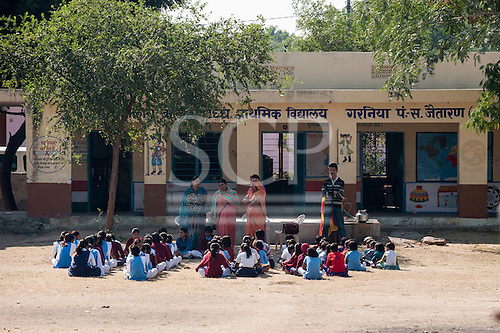 Rajasthan, India. Between Jodhpur and Jaipur. Primary school with children and teachers; lesson outside under a tree.