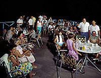 A large barbecue party outside at night.