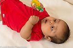 3 month old baby boy on back closeup interested in toy rattle he holds