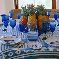 A laid table featuring blue glassware and crockery and a plate of pineapples on an Ikat tablecloth