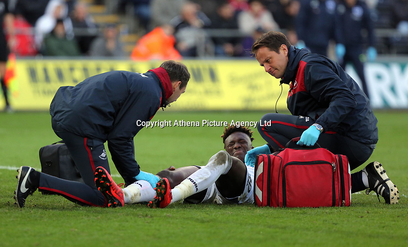 Tammy Abraham of Swansea City (C) is seen to by team physiotherapists during the Premier League match between Swansea City and Brighton and Hove Albion at The Liberty Stadium, Swansea, Wales, UK. Saturday 04 November 2017