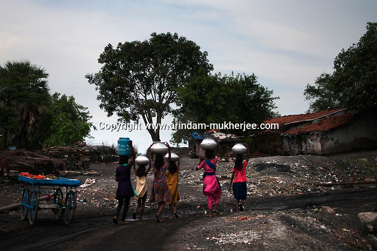 Young girls carrying clean drinking water to their houses at Deepu Dhowra slum area in Jharia. This area is affected by mine fire causing damage to the water pipes .A huge coal mine fire is engulfing the city of Jharia from all its sides. All scientific efforts have gone in vain to stop this raging fire. This fire is affecting lives of people living in and around Jharia. Jharkhand, India. Arindam Mukherjee