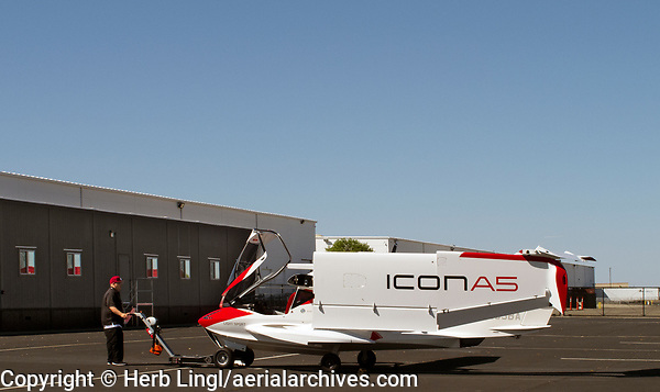 An ICON A5 with folded wings at ICON Aircraft headquarters at the Nut Tree airport (VCB) in Vacaville, Solano County, California is being towed back into the hangar after a flight.<br /> <br /> Partnership interests in brand new ICON A5 aircraft based in the San Francisco Bay Area and at Clear Lake are available.  Please visit:<br /> <br /> http://aerialarchives.com/ICON-A5-Aircraft-Partnership.htm<br /> <br /> Details about a tour of the Nut Tree A5 assembly line in Vacaville are available at:<br /> <br /> http://aerialarchives.com/blog/2019/icon-a5-amphibious-light-sport-aircraft