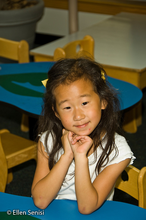 MR / College Park, Maryland.Center for Young Children, laboratory school within the College of Education at the University of Maryland. Full day developmental program of early childhood education for children of faculty, staff, and students at the university..Portrait of girl (5, Korean-American) in school..MR: Jeo1.© Ellen B. Senisi