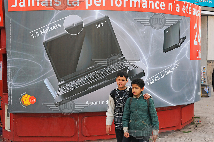 Two boys walk past an advert for Lenovo, a Chinese-based multinational technology firm, laptop computers.