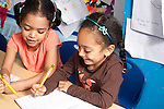Education Preschool 3-4 year olds two girls playing together writing activity using pencils