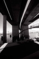 Three people on walkway under overpass<br />