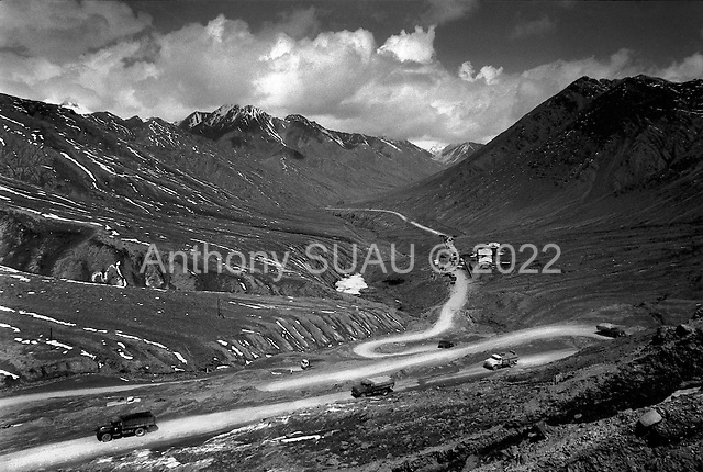 """Horag - Osh Road Tajikistan .1996.Trucks make ther way up the old silk road to a check point at the Tajik/Kyrgyzstan border. Trucks are checked for hidden opium or """"hannka"""" much of which is destined for Western Europe.."""