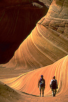 Hikers walking amidst the orange sandstone waves of Vermilion Cliffs in Paria Canton, Arizona.<br />
