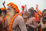 After much preparation, the thousands of Naga sadhus jubilantly make their way to the holy river to bathe. The red bag contains sacred ash to smear on again after bathing.
