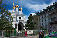 """Switzerland. Geneva.The Russian Church (full name: Cathédrale de l'Exaltation de la Sainte Croix) is designed in a Byzantine Moscovite style. The church is a lovely 19th-century Russian Orthodox church topped with golden onion domes. The church, facade. roof and all onion domes underwent a complete revival restoration. The newly restored bulbs are gilded with golden leaves. The term gilding covers a number of decorative techniques for applying fine gold leaf to solid surfaces such as onion domes and crosses. A gilded object is also described as """"gilt"""". Tourists snap pictures of the church. Two young women are taking a """"selfie"""" with their cell phone.The Russian church serves today not only the Russian community but also Bulgarians, Serbs, Coptic Christians and other Orthodox worshippers who do not have their own church in Geneva. An onion dome is a dome whose shape resembles an onion. Such domes are often larger in diameter than the drum upon which they sit, and their height usually exceeds their width. These bulbous structures taper smoothly to a point. 10.08.2017 © 2017 Didier Ruef"""