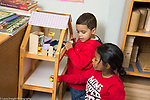 Education preschool 3 year olds two boys  playing with doll house dolls and furniture