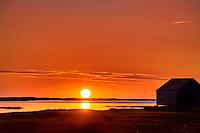 Sunrise over salt pond with boat house silhouette, Eastham, Cape Cod, MA, USA