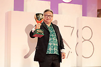 """VENICE, ITALY - SEPTEMBER 11: Director Erik Matti poses, on behalf of actor John Arcilla, with the Coppa Volpi for Best Actor for """"On the Job: The Missing 8"""" at the awards winner photocall during the 78th Venice International Film Festival on September 11, 2021 in Venice, Italy."""