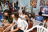 """Thailand. Bangkok. Tha Tian. A group of boys play on PlayStation 3. The PlayStation 3, commonly abbreviated PS3, is the third home video game console produced by Sony Computer Entertainment, and the successor to the PlayStation 2 as part of the PlayStation series. Television and plastic chairs. Pictures of american wrestlers and King Bhumibol are taped on the wall. Bhumibol Adulyadej (born 5 December 1927), is the current King and Head of the State of Thailand. Publicly acclaimed """"the Great"""" he is also known as Rama IX. Having reigned since 9 June 1946, he is the world's longest-serving current head of state and the longest-serving monarch in Thai history. Tha Tian is a community located in the downtown area and in the center of the urban historic district, called Koh Rattanakosin. 02.04.09 © 2009 Didier Ruef"""