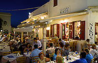 Night photo of beautiful Mykonos Greece and restaurant called Taverna Nikos in downtown shopping