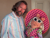 """Miss Piggy  and companion Jim Henson take a break from reporters in May 1989 in Los Angeles to talk about """"The Jim Henson Hour,"""" a magazine style show to be aired by NBC that mixes half hour """"The Storyteller"""" dramatic pieces , """"Miss Piggy's Hollywood,"""" and  Muppet creatures in various pieces. """"I think we've always pushed puppetry to the limits,"""" says Henson. """"Now we're pushing new technologies to the limit. (Photo by Alan Greth)"""