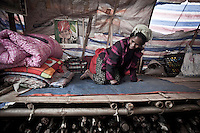 A Kachin elder woman crowls as she grumbles inside a tent settled at Seng Mai Pa IDP camp, one of the multiple camps settled outskirsts of Maiya Jang city. The camp gives shelter to two thousand displaced persons from the war-torn villages in Kachin State. The KIA positions around Maiya Jang city have been attacked by shelling and heavy artillery during months. Fierce clashes have taken place since the ceasefire was broken out by the Burmese army last June 2011. During months the fighting were spread out along the Kachin State leaving more than 40,000 displaced persons and refugees (a conservative estimating) in accord with the humanitarian aid groups.