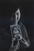 "Mrs Zhang, 31, holds a picture of her son Zhang Zheng who was stolen 8th May 2003.  Message reads ""Zhang Zheng, mummy is missing you.""..PHOTO BY SINOPIX"